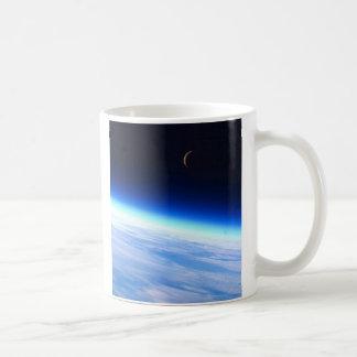 Luna creciente sobre una tierra que brilla intensa tazas de café