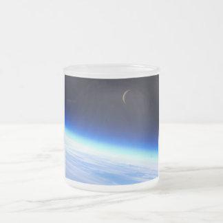 Luna creciente sobre una tierra que brilla intensa taza