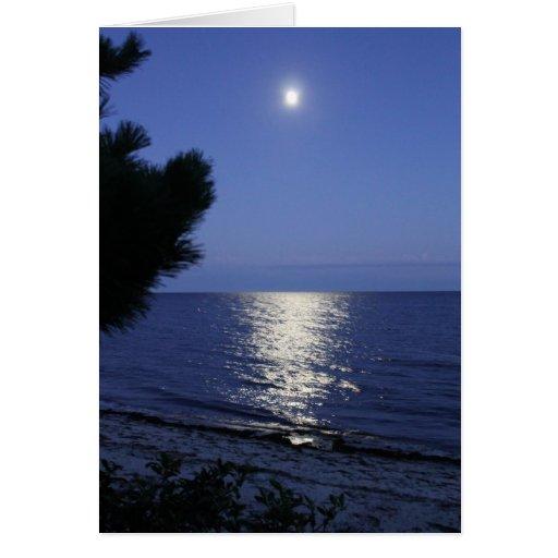 Luna que sube sobre tarjeta de nota del océano