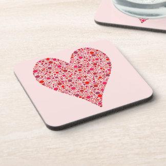Lunares carmesís de la forma del corazón en rosa posavasos de bebida