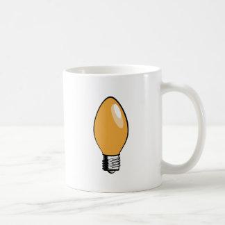 Luz anaranjada del árbol de navidad taza de café