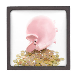Lying pink piggy bank with pile of euro coins gift box