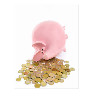 Lying pink piggy bank with pile of euro coins postcard