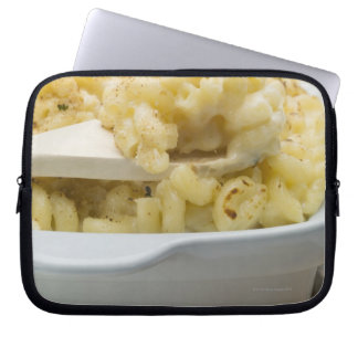 Macaroni cheese in baking dish with wooden computer sleeve