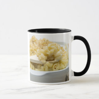 Macaroni cheese in baking dish with wooden mug