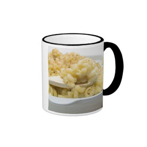 Macaroni cheese in baking dish with wooden coffee mugs
