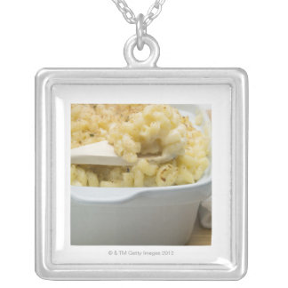 Macaroni cheese in baking dish with wooden silver plated necklace