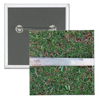Machete on a grassy ground pinback button