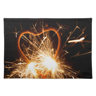 Macro photo of a burning sparkler in form of a hea placemat