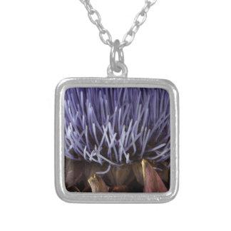 Macro photo of blue artichoke flower leaves. square pendant necklace