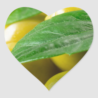 Macro view of the olives with green leaves closeup heart sticker