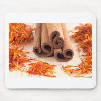 Macro view of the sticks of cinnamon and saffron mouse pad