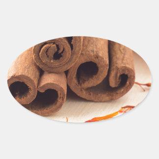 Macro view of the sticks of cinnamon and saffron oval sticker