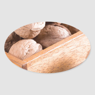 Macro view of walnuts close up in a wooden box oval sticker