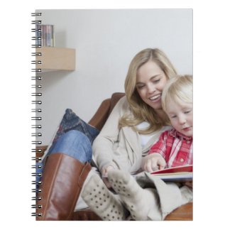 Madre e hijo que se sientan en el sofá junto libreta