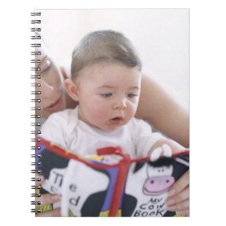Madre que lee al bebé. Caras de una madre Note Book