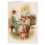 Madre y niños del vintage con la tarjeta del piano
