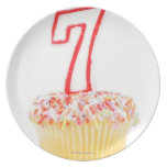 Magdalena con una vela numerada 7 del cumpleaños platos de comidas