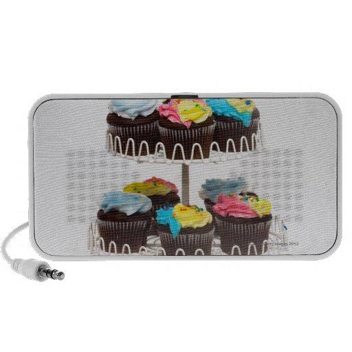Magdalenas del chocolate en un soporte de la torta mini altavoz