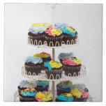Magdalenas del chocolate en un soporte de la torta azulejo cuadrado grande