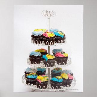 Magdalenas del chocolate en un soporte de la torta póster