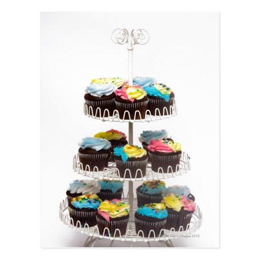 Magdalenas del chocolate en un soporte de la torta postal