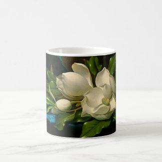Magnolias gigantes en una taza azul del paño del t