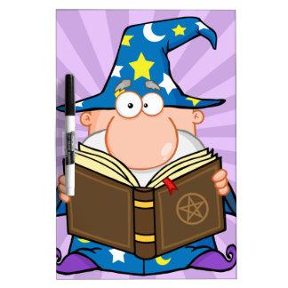 Mago divertido que sostiene un libro mágico pizarras blancas de calidad