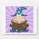 Mago divertido que sostiene un libro mágico tapete de raton