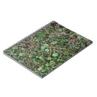 Malas hierbas en campo de hierba spiral notebooks