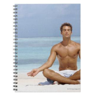 Maldivas, hombre joven hermoso meditating en a libro de apuntes con espiral