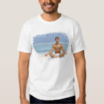 Maldives, Handsome young man meditating in a T-Shirt