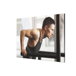 Male athlete using gymnastics equipment in gym canvas print