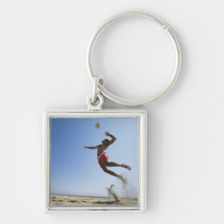 Male beach volleyball player jumping up to spike key chains