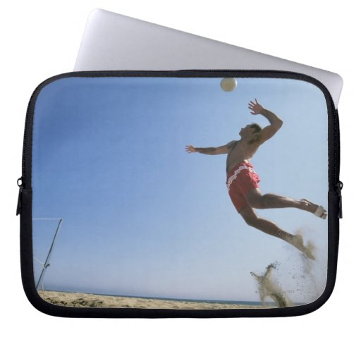 Male beach volleyball player jumping up to spike laptop computer sleeves