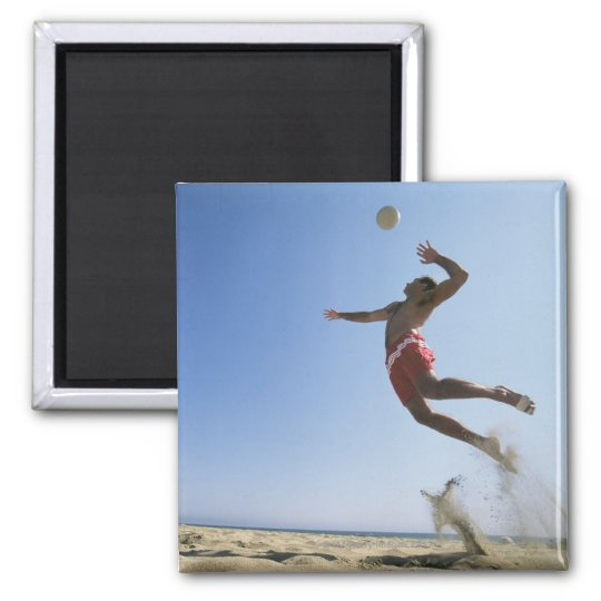 Male beach volleyball player jumping up to spike magnet