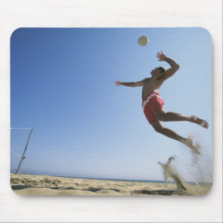 Male beach volleyball player jumping up to spike mouse pad