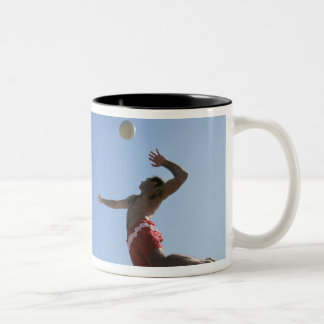 Male beach volleyball player jumping up to spike coffee mugs