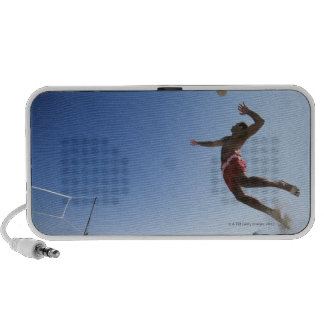 Male beach volleyball player jumping up to spike iPhone speaker
