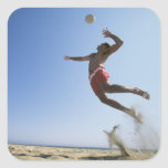 Male beach volleyball player jumping up to spike square sticker