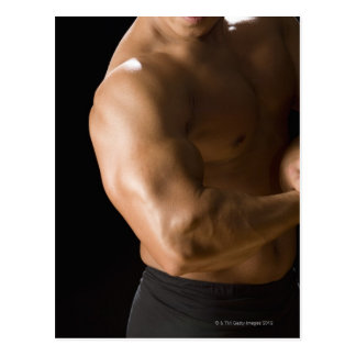 Male bodybuilder flexing muscles, front view, 2 postcard