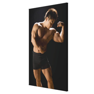 Male bodybuilder flexing muscles, front view, canvas print