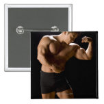 Male bodybuilder flexing muscles, front view, pinback button
