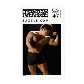 Male bodybuilder flexing muscles, front view, postage