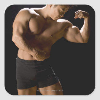Male bodybuilder flexing muscles, front view, square sticker
