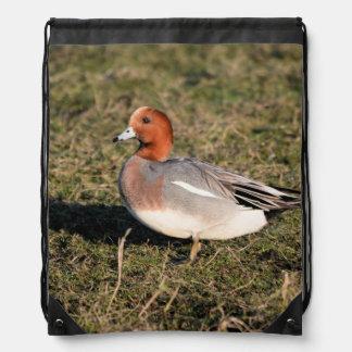 male Eurasian Wigeon Duck walks in a grassy field Drawstring Bag