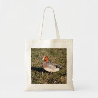 male Eurasian Wigeon Duck walks in a grassy field Tote Bag
