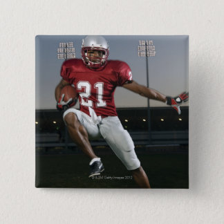 Male football player carrying football pinback button