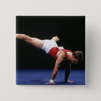 Male gymnast peforming a routine in the floor button