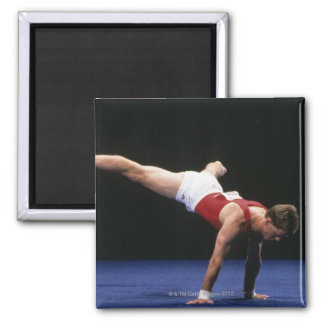 Male gymnast peforming a routine in the floor magnets